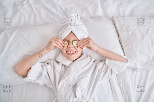 Cheerful kid with slices of cucumber on yes lying on bed