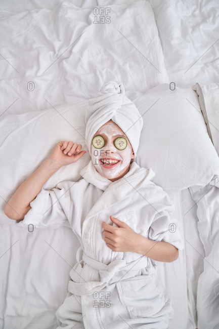 Playful kid with facial mask lying on bed