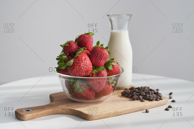 From above bowl of ripe strawberries and heap of chocolate pellets placed on napkin and cutting board near bottle of milk on kitchen table in morning