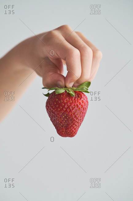 Cropped anonymous kid demonstrating fresh strawberries on his hand on blurred background