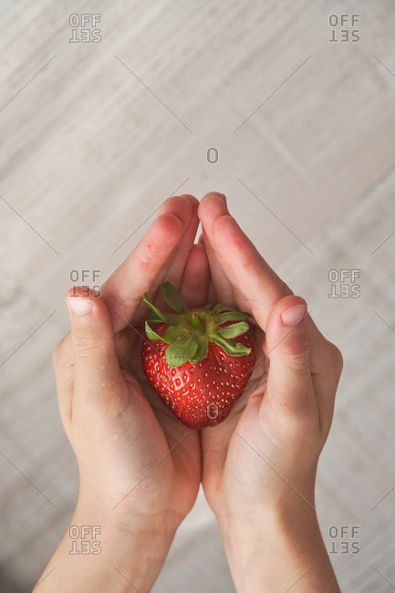 From above top view of anonymous kid demonstrating fresh strawberry on his hands on blurred background