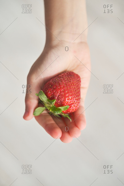 From above top view of anonymous kid demonstrating fresh strawberry on his hand on blurred background