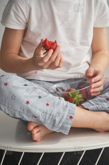 Cropped unrecognizable boy in sleepwear eating sweet strawberry while sitting cross legged at home