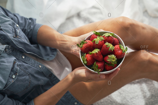 From above anonymous female demonstrating bowl of ripe strawberries while sitting on bed at home on summer day