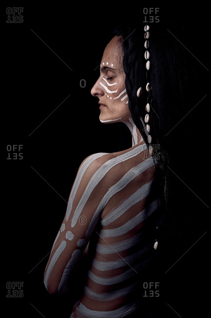 Side view of naked tender beautiful brunette Native American woman with white striped painted on body covering breast standing in dark on black background
