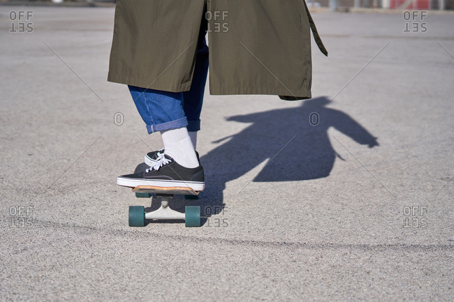A Man skating on a skateboard on the road with his raincoat and sunglasses