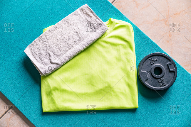 From above sports set for sportsman consisting of towel on vibrant green active wear in composition with turquoise sports mat and black round weight prepared for comforting training in contemporary fitness center