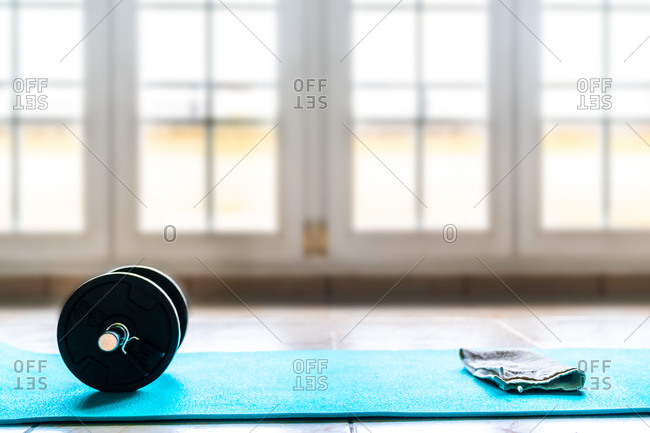 From above sports set for training consisting of black collapsible dumbbell and white towel on light blue sports mat on floor against blurred window wall in spacious contemporary gym