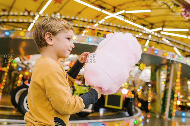 Side view of delighted boy smiling and eating sweet candy floss while standing at funfair