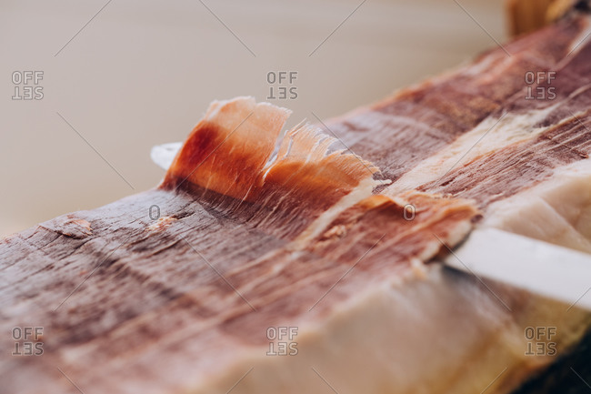 From above view of knife cutting thin slice of ham with tallow lines