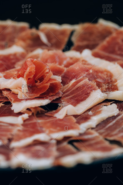 From above view of thin slices of ham with tallow lines served in plate on black background
