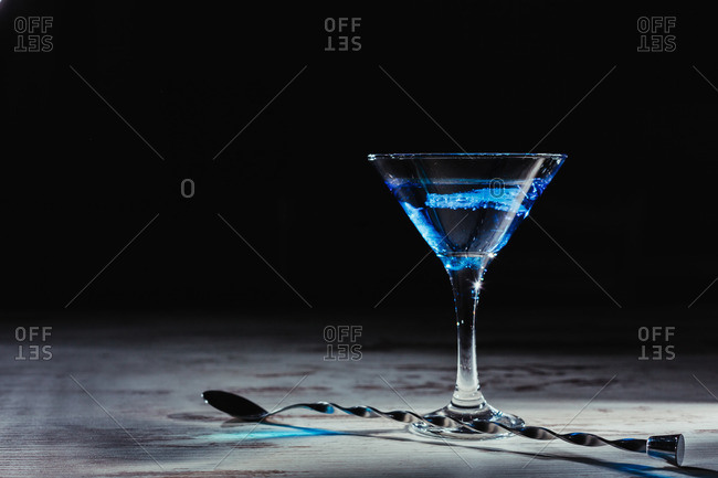 Glass of vivid blue cocktail and twisted spoon on rustic table
