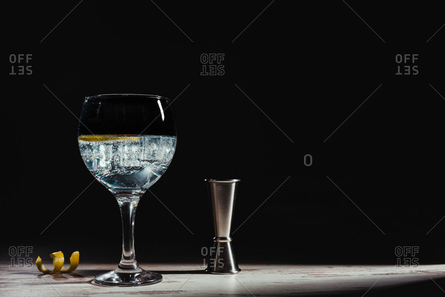 Transparent glass of tasty gin tonic cocktail with ice in arrangement with lemon twist peel and jigger on table in light rays against black background