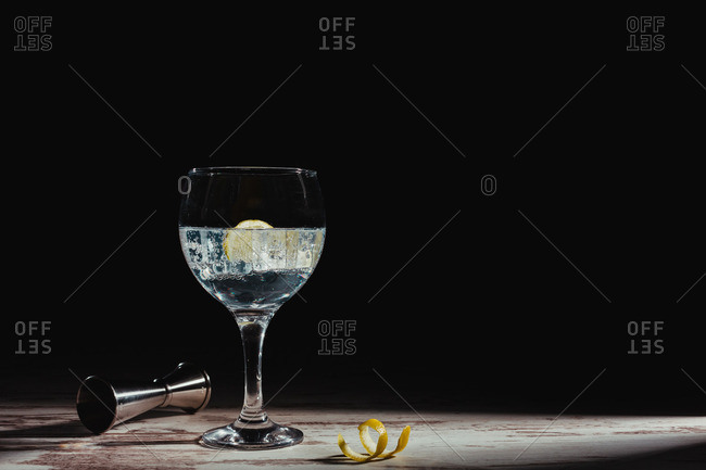 Glass of gin tonic in composition with lemon and jigger on table in dark room