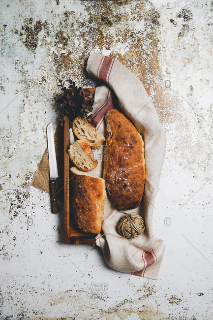 From above rustic composition with aromatic bread loaves on board with linen towel and knife on shabby surface