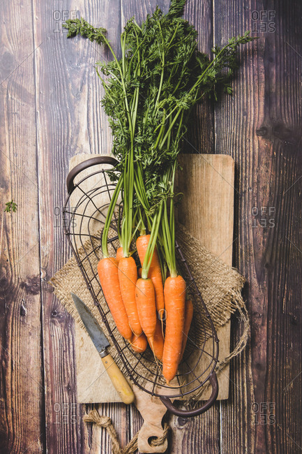 Top view of harvested ripe carrots with green foliage placed on cutting board on wooden table