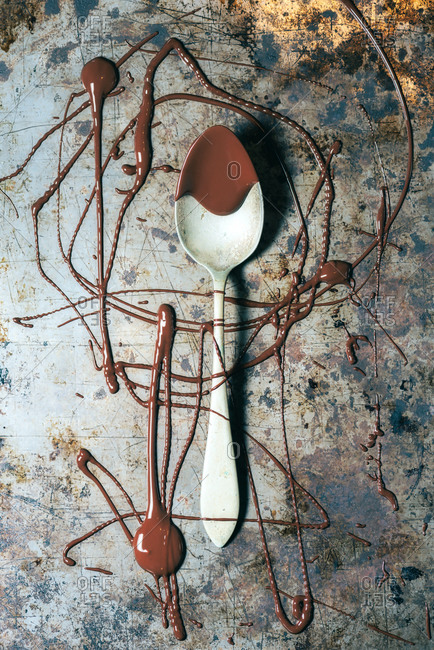 From above top view spoon with chocolate spilled over rustic metal surface background