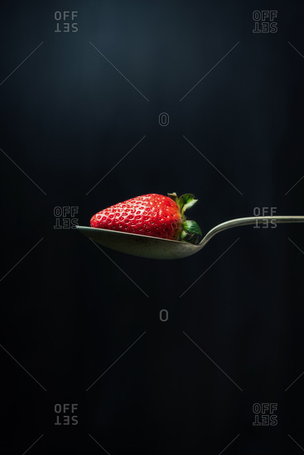 Strawberry in a spoon on dark background
