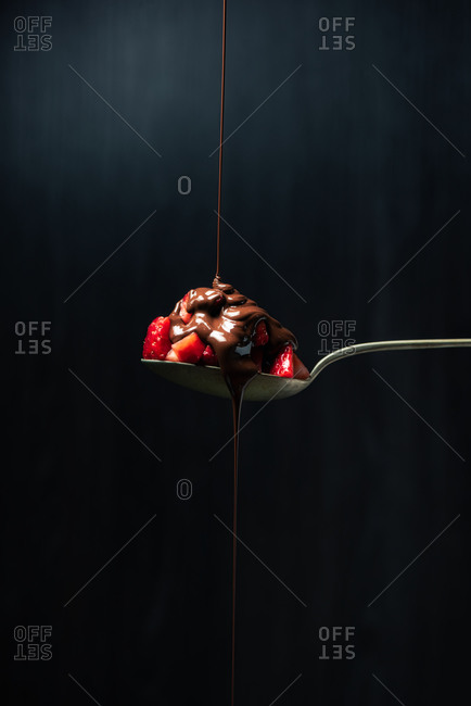 Delicious chocolate ganache jet of chocolate falling on top of a strawberry perched on a spoon
