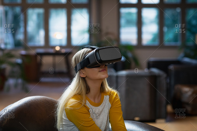 Self isolation in lockdown quarantine. side view of a young caucasian woman enjoying time at home, sitting in sitting room and using vr headset.