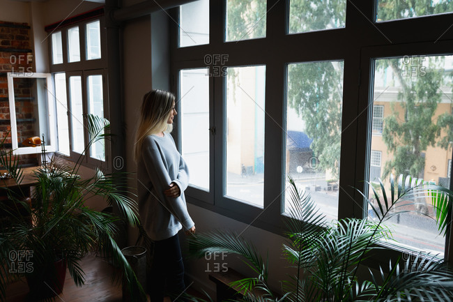 Self isolation in lockdown quarantine. side view of a young caucasian woman enjoying time at home, wearing grey sweater, standing by the window and looking through it.
