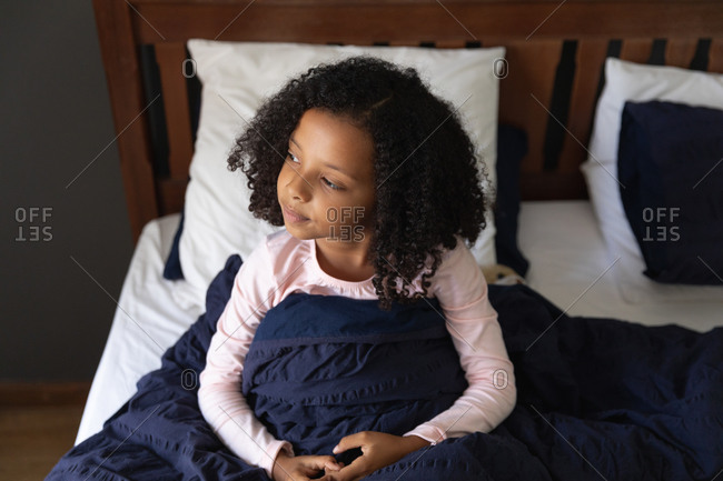 African American girl waking up in her father bedroom on a sunny morning, during social distancing at home during quarantine lockdown.