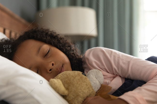 African American girl sleeping in her father bedroom and embracing a teddy bear, during social distancing at home during quarantine lockdown.