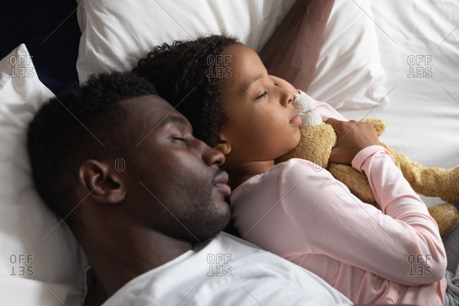 African American girl and her father social distancing at home during quarantine lockdown, spending time together, embracing while sleeping.