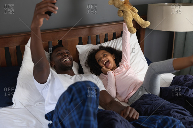 African American girl and her father social distancing at home during quarantine lockdown, spending time together, having fun and taking a selfie with a smartphone.