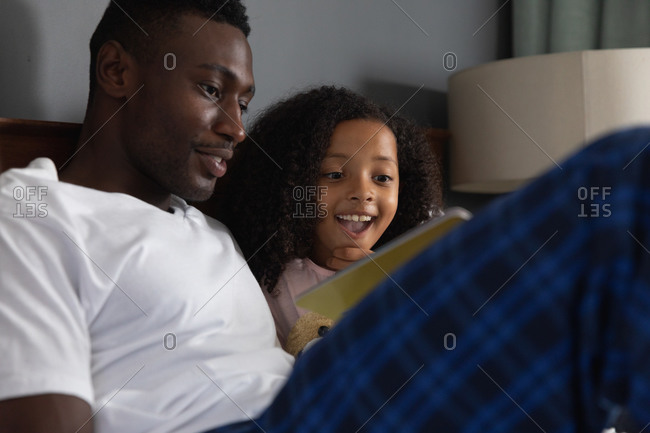 African American girl and her father social distancing at home during quarantine lockdown, spending time together, having fun and reading a book in a bed.