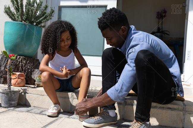 African American girl and her father social distancing at home during quarantine lockdown, spending time together in their garden. Dad is helping his daughter tying shoe lace.