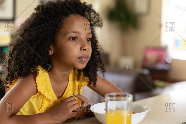African American girl, social distancing at home during quarantine lockdown, sitting by a table and having her breakfast and a glass of orange juice.