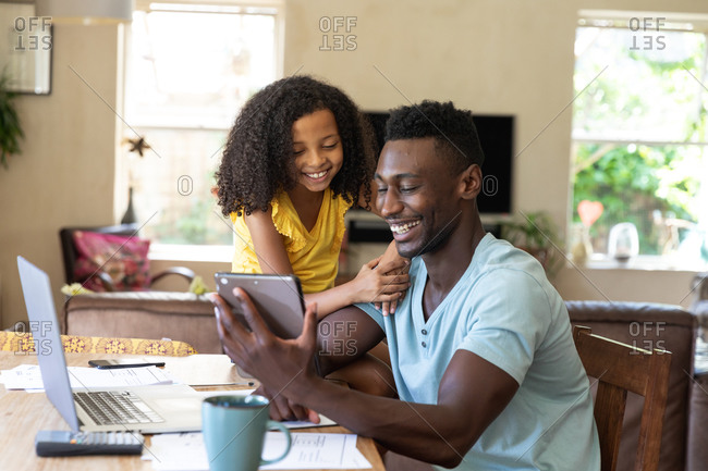 African American girl wearing a yellow blouse, social distancing at home during quarantine lockdown, spending time with her father using a tablet.