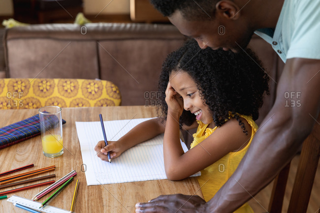 African American girl wearing a yellow blouse, social distancing at home during quarantine lockdown, sitting by a table and drawing pictures with her dad.
