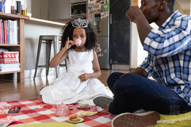 African American girl wearing a toy crown, social distancing at home during quarantine lockdown, playing with her dad, having a doll tea party.