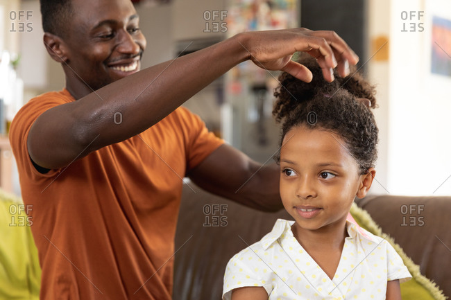 African American man wearing an orange t-shirt, social distancing at home during quarantine lockdown, doing a ponytail to his daughter wearing a white shirt.