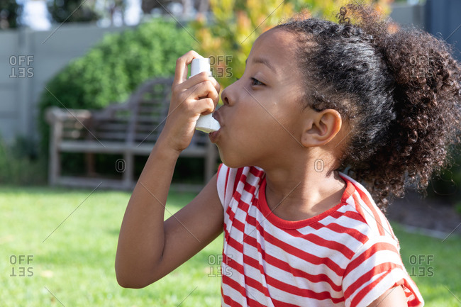 African American girl social distancing at home during quarantine lockdown, wearing a stripped t-shirt, using her inhaler, in a garden on a sunny day.