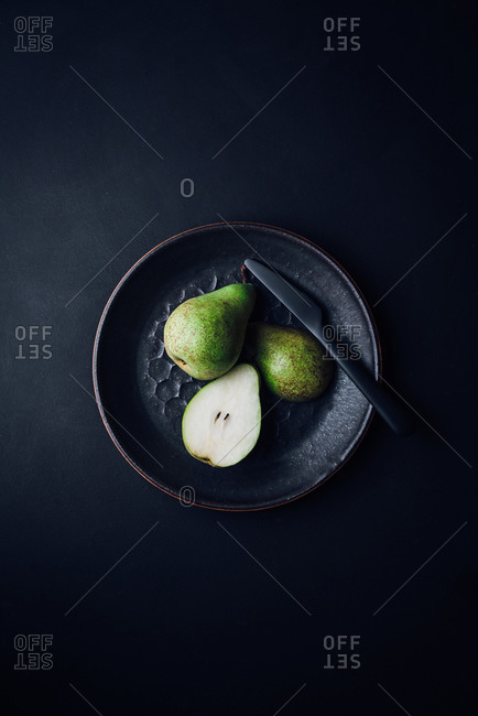 Minimalistic pears on a plate on black surface