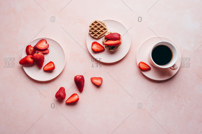 Strawberries and waffles on pink background from above