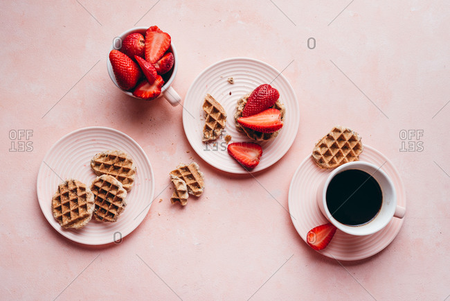 Strawberries and waffles on pink background with coffee from above