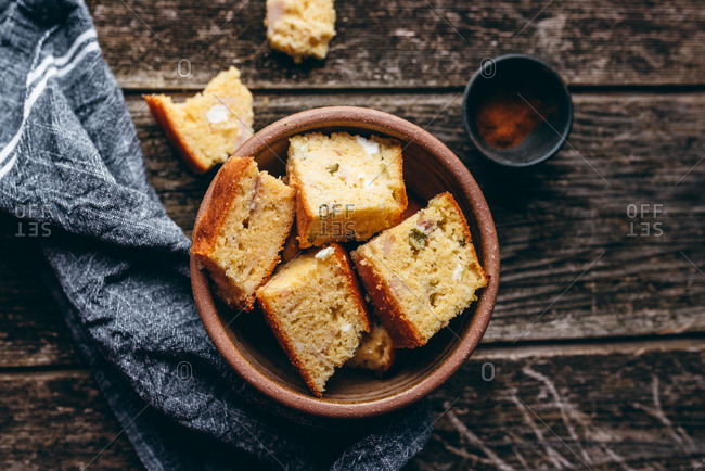 Homemade corn bread in a bowl on rustic wood