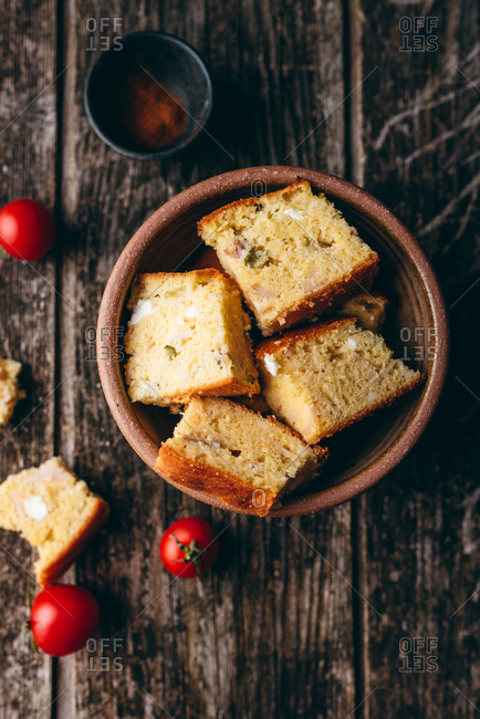 Homemade corn bread in a bowl beside cherry tomatoes on rustic wood