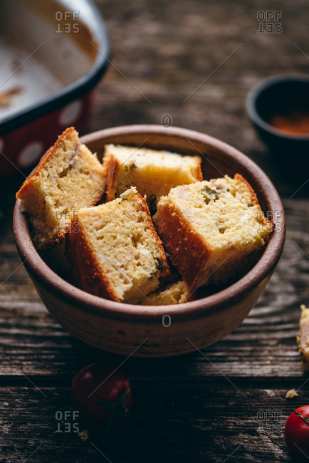 Close up of homemade corn bread in a bowl on rustic wood