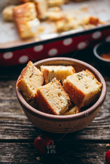 Close up of homemade corn bread served in a bowl on rustic wood table