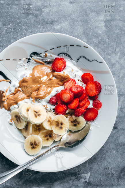 Granola with bananas and strawberries on gray background
