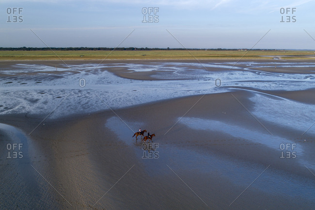 Aerial of riders in the Wadden Sea at low tide, Sankt Peter-Ording, Schleswig-Holstein, Germany