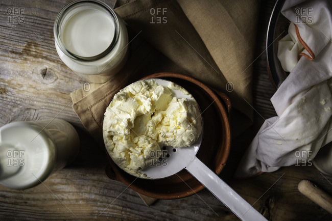 Homemade mascarpone cheese with a slotted spoon on a vintage atmosphere