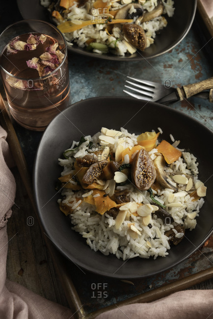 Vegetarian rice with dried fruits carrots and mushrooms served with rosebuds infused water