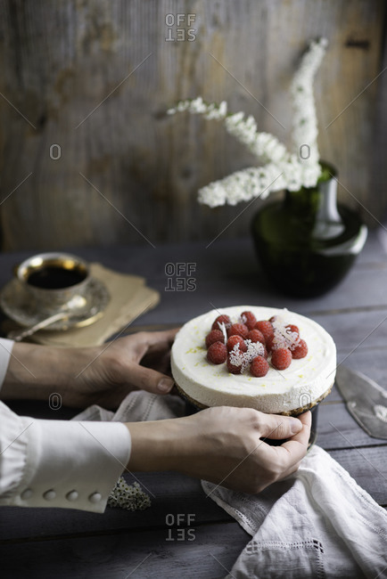Uncooked creamy cheesecake decorated with fresh raspberries ready to get shared