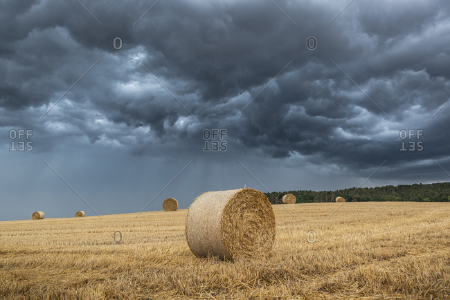 Storm over a stubble field at sunset, Thuringia, Germany